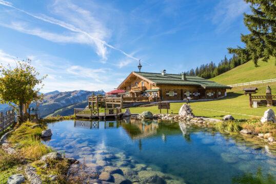 Garten Inspiration in alpiner Umgebung mit Schwimmteich – Beispiel mit kleiner Terrasse am Tei...