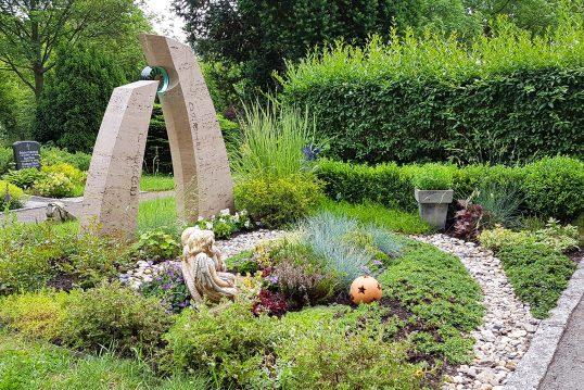 Moderne Grabgestaltung mit Kies  Bodendeckern & Gräsern einer Doppelgrabanlage - zweiteiliger Grabstein aus Kalkstein mit Glaselement