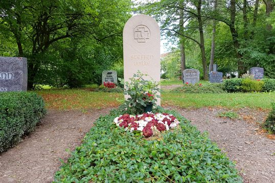 Pflegeleichte ganzjährige Grabbepflanzung mit Bodendeckern auf einem Einzelgrab mit modernem Grabstein aus Kalkstein