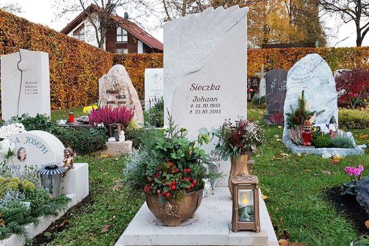 pflegeleichte Grabgestaltung zu Allerheiligen eines Urnengrabes mit Grabstein aus Kalkstein & Abdeckplatte - Grabschmuck mit bepflanzter Grabschale aus Bronze passender Vase und Grablaterne