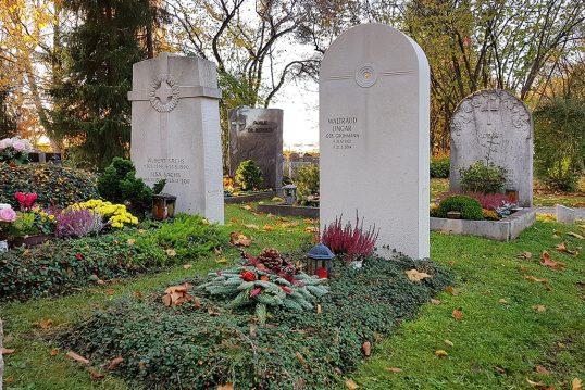 Schönes Einzelgrab mit halbrunden Grabstein aus Kalkstein & christlichem Symbol - Grabgestaltung zu Allerhieligen mit Reisig & Grabgesteck