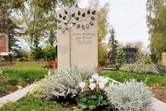 Grabmal für ein Einzelgrab aus Kalkstein mit Grabumfassung - moderne Grabgestaltung mit schöner Grabbepflanzung