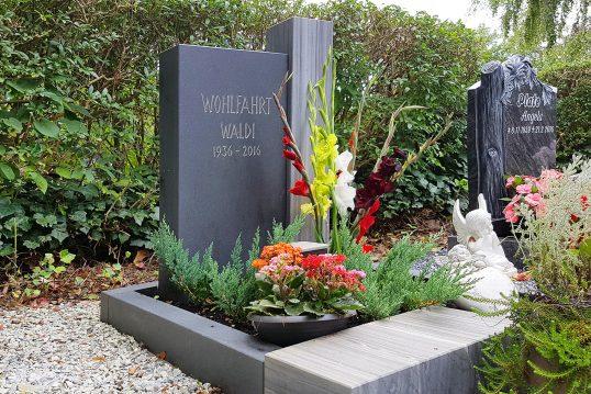 Modern gestaltetes Urnengrab mit Granitgrabstein und Einfassung - Pflegeleichte Grabgestaltung mit einer Konifere und Blumen