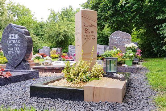 Modernes Urnengrab mit Stele aus Sandstein poliert und einer Einfassung aus Granit & Sandstein - pflegeleichte Grabgestaltung mit Kies und Bodendeckern