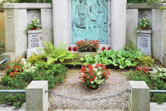 Historisches Familiengrab aus Granit mit einer figürlichen Darstellung auf einer Br...
