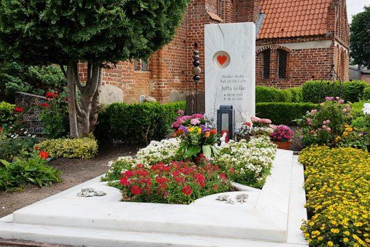 Moderner Einzelgrabstein mit aufwendig gestalteter Grabumfassung aus weißem Marmor - prachtvolle Bepflanzung für den Sommer mit blühenden Grabpflanzen