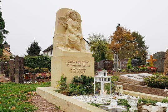 Kindergrab mit aufwendig gearbeitetem Engelgrabstein und Grabeinfassung aus Sandstein - winterliche Grabgestaltung mit Kies  Reisig & Grabschmuck