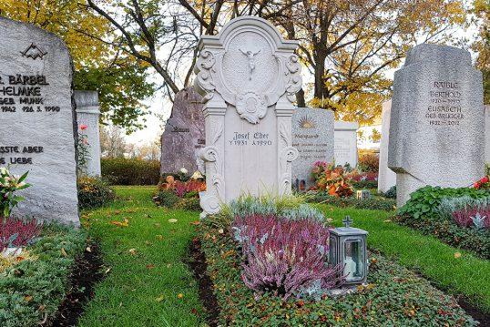 Klassisches Einzelgrab mit aufwendig verziertem Grabstein mit christlichem Motiv - pflegeleichte Grabbepflanzung mit Blumen & immergrünen Bodendeckern
