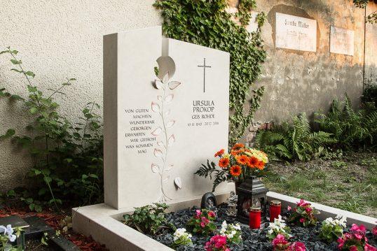 Gestaltungsbeispiel für ein modernes Einzelgrab aus Kalkstein - Grabgestaltung mit Rindenmulch & Blumen - Grablaternen & Grabfiguren
