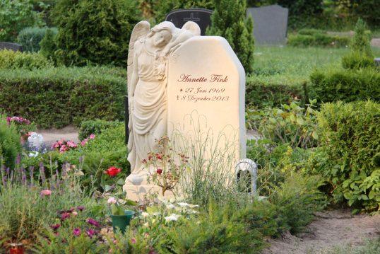 Sandstein Engel Grabstein für ein Einzelgrab mit sommerlicher Grabbepflanzung
