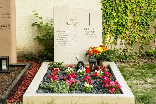 Modernes Einzelgrab aus Kalkstein mit Grabspruch und ausgearbeiteter Blattranke