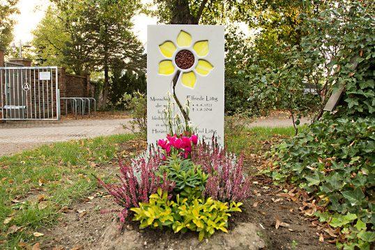 Idee für die Grabgestaltung – Einzelgrabstein aus hellem Kalkstein mit Blume ...