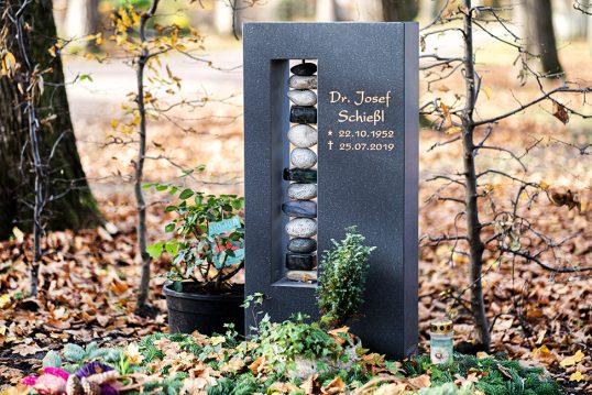 Modern gestalteter Urnengrabstein aus poliertem Granit mit Kieselsteinsäule in eine...