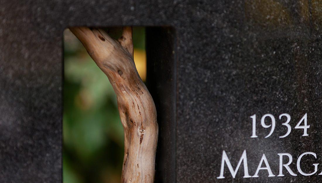 Urnengrab Beispielgestaltung –  Moderner Granitgrabstein mit Öffnung und Olivenholzzweig & Grabeinfassung – Schlichter Grabschmuck