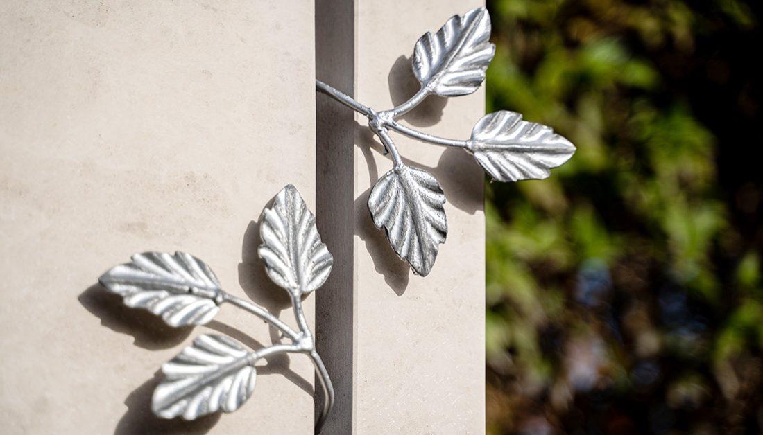 Beispiel für eine Urnengrabgestaltung mit moderner Kalkstein-Stele & Metallelement – Grabbepflanzung mit Strauchrosen
