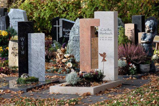 Moderner Urnengrabstein aus hellem Kalkstein und Rotem Travertin mit Holzwürfeln ve...