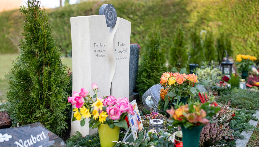 Beispiel Grabgestaltung eines modernen Urnengrabmales aus Kalkstein mit Kristallen – winterliche Grabeindeckung mit Reisig & Blumen