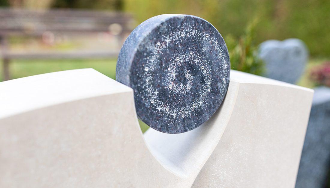 Urnengrab Gestaltungsidee – Moderner Urnengrabstein mit Spirale und Sternen aus Kristallen – winterliche Grabeindeckung mit Tannengrün