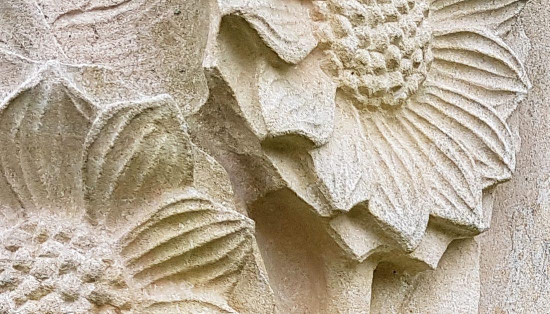 Einzelgrabstein mit Sonnenblumengravur aus Sandstein und pflegeleichter Grabbepflanzung mit Stauden