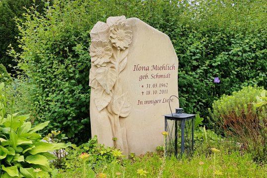 Einzelgrabstein mit Sonnenblumengravur aus Sandstein und pflegeleichter Grabbepflan...