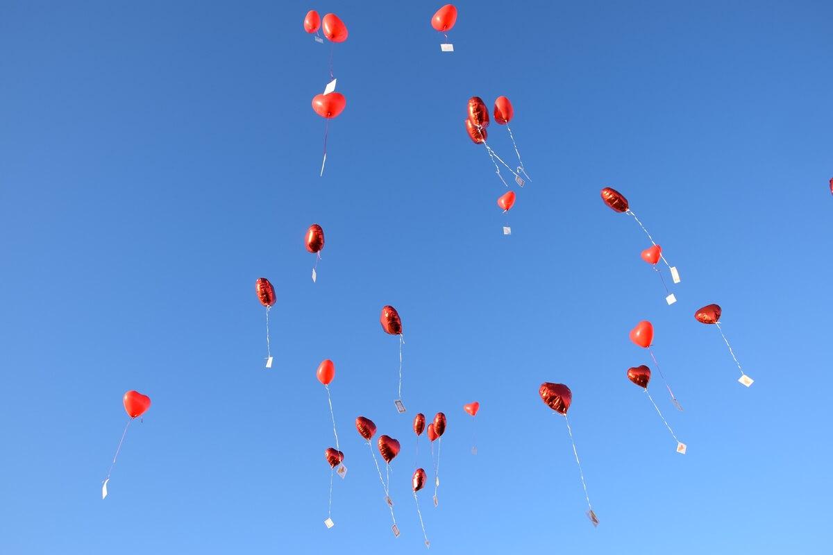 Rote Herzluftballons fliegen gen Himmel