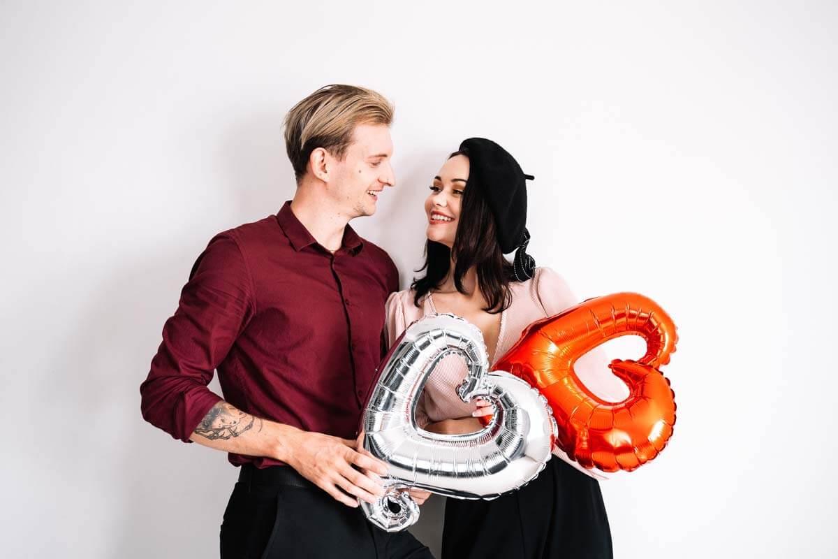 Liebespaar mit Heliumballons in Herzform