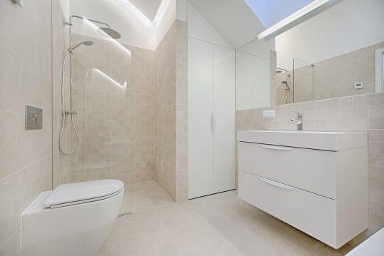 Modernes Bad im Bauhaustyle mit ebenerdiger Dusche und eingebautem Wandschrank in hellem beige