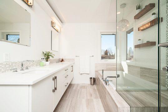 Moderne Badezimmereinrichtung in weiß und Bodenfliesen in Holzoptik – eckige Einbau-Badewanne & großer Waschtisch-Schrank
