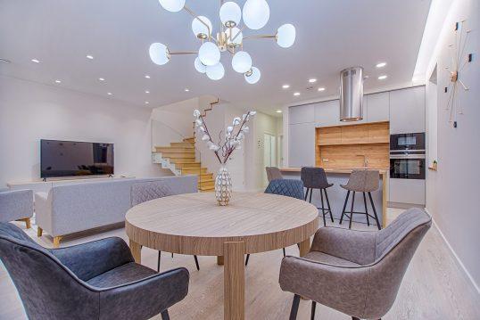 Wohnidee für eine Essecke im modernen Appartment mit rundem Esstisch aus Holz und Ledersesseln