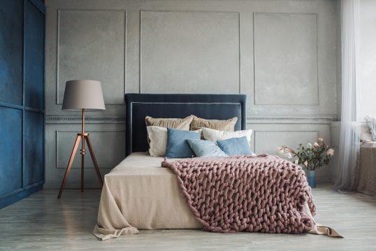 Schlafzimmer Wohnidee – Barockes Schlafzimmer modern interpretiert – Kingsize-Bett in blauem Samt vor grauer Wandvertäfelung