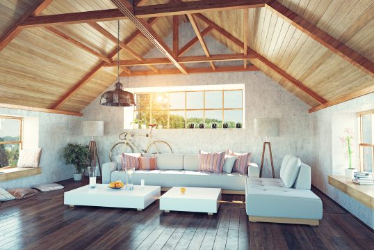 Modernes helles Dachgeschoß mit Holzvertäfelung und freiliegenden Balken – gemütliches Dreisitzer-Sofa aus hellem Stoff