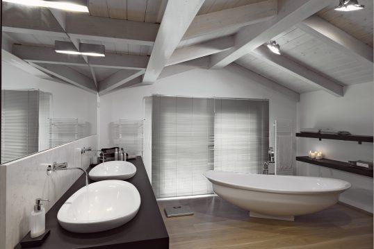Beispiel für ein modern eingerichtetes Badezimmer im Dachgeschoß mit Eichendielen – Badezimmer Wohnidee mit freistehende ovale Badewanne & Doppelwaschtisch aus Keramik – schwarze Wandregale