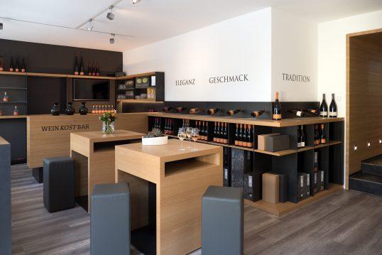 Weinkeller moderner Bauhausstil mit offenen Weinregalen & Holztischen und Lede...