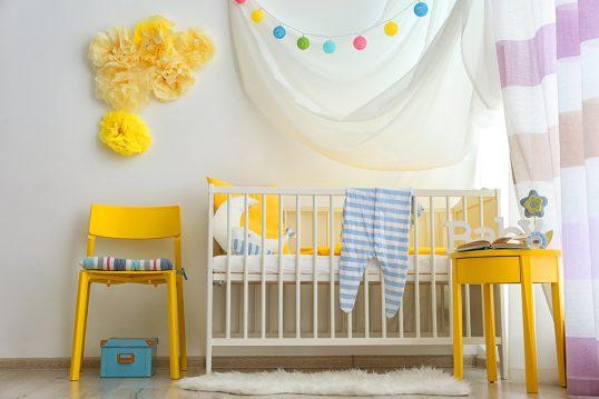 Babyzimmer für Mädchen Idee mit weißen Babybett  gelben Stuhl & gelbe Schränkchen - interessante Wandgestaltung mit gelben Tüll zum nachmachen - bunte Lichterkette