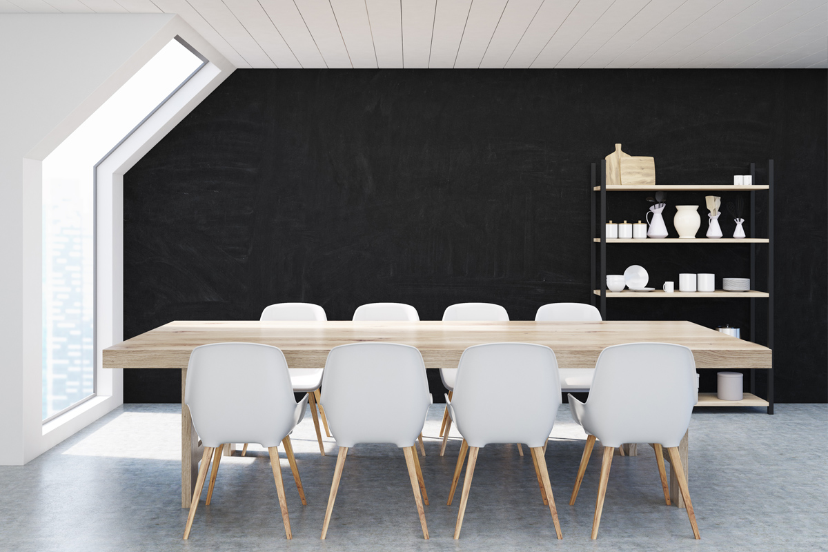 Esszimmer mit hellen Möbeln und schwarzer Rückwand