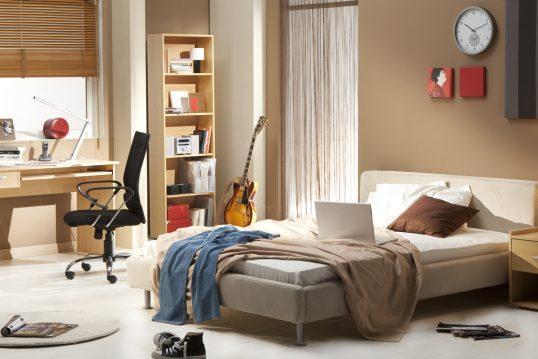 Gestaltungsidee für ein Jungen Jugendzimmer mit beiger Wand – Großes Polsterbett – Holzbücherregal  Holzschreibtisch mit Schreibtischstuhl & Leselampe – Runder Teppich in grau
