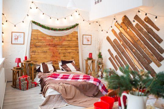 Wohnidee – Jugendzimmer für Jungs mit weihnachtlicher Dekoration – Großes Doppelbett mit vielen Decken & Beistelltische – stilvolle Holzverkleidung an den Wänden – Lichterkette für schönes Lichtambiente