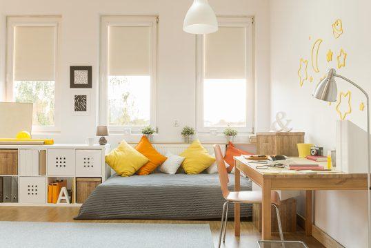 Jugendzimmer für Mädchen Idee mit orangenen Akzenten – Schlafsofa mit vielen Kissen – Schreibtisch kombiniert mit orangenen Stuhl & Schreibtischlampe – weiße Hängelampe – weißes Regal