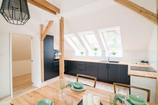 Moderne Kücheneinrichtung unter der Dachschräge – Beispiel mit schwarzer Küchenzeile & Holzarbeitsfläche – Holz Esstisch & Stühle – schwarze Hängelampe & kleine Zimmerpflanzen