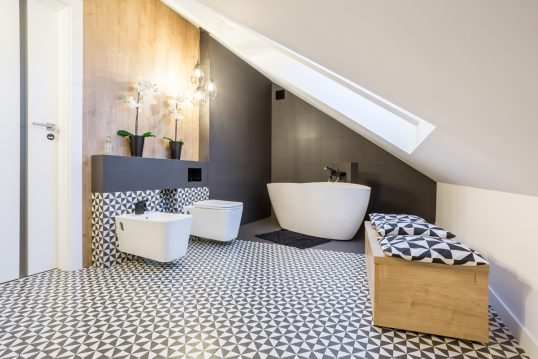 Moderne Einrichtungsidee für ein Bad im Dachgeschoss – Beispiel mit freistehender Badewanne & Holzbank – schwarz-weiße Wandfliesen & Holzakzente