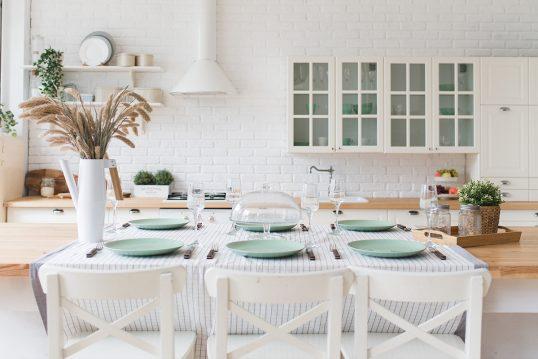 Dekorierter Tisch in einer weißen Landhausküche als Wohnidee – Beispiel mit g...