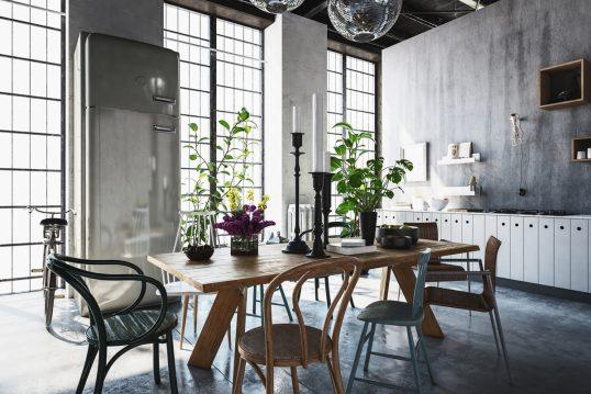 Industrielle Küche mit dekoriertem Tisch als Wohnidee – Beispiel mit Holztisch & Holzstühlen – hohe Kerzenständer in schwarz & verschiedene Vasen