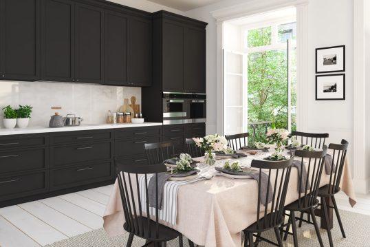Geräumige schwarze Küche mit sommerlich gedecktem Esstisch als Inspiration – Beispiel mit moderner Esstisch Deko – pinke Tischdecke & Tischläufer – große Servietten & Glasvasen mit Blumen