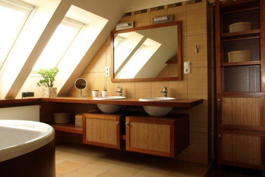 Kleines Badezimmer mit Dachschräge & zwei Waschbecken im Landhausstil – Beispiel mit Waschbeckenschränken aus Holz – großer Spiegel & Spiegelleuchten