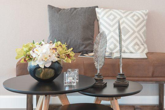 Idee für einen Sitzbereich mit Liegesofa & dekorierten Beistelltischen - Blumenstrauß in dunkler Vase  Teelichter & Dekofiguren in Form von Federn