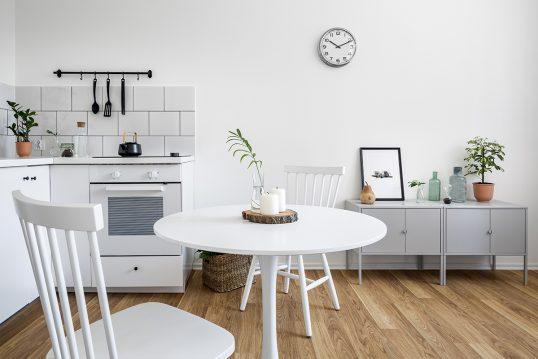 Wohnidee – Weiße Küche mit Holzboden & runder Küchentisch mit Alltags-De...