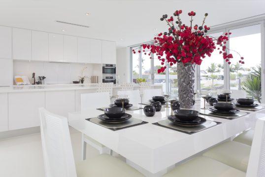 Gestaltungsbeispiel für eine weiße moderne Küche mit schwarz-weißer Tischdekoration...
