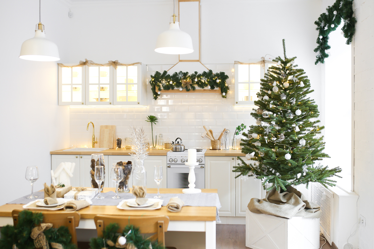 Kleiner Weihnachtsbaum mit dezentem Schmuck in Silber und weiß in der Küche