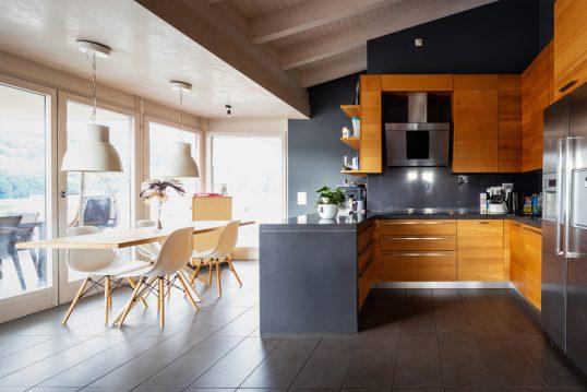 Moderne Idee für ein Appartement unter dem Dach - Beispiel mit Küche & Essbereich direkt unter der Dachschräge - Küche aus Holz - Esstisch mit Schalenstühlen & Hängelampe