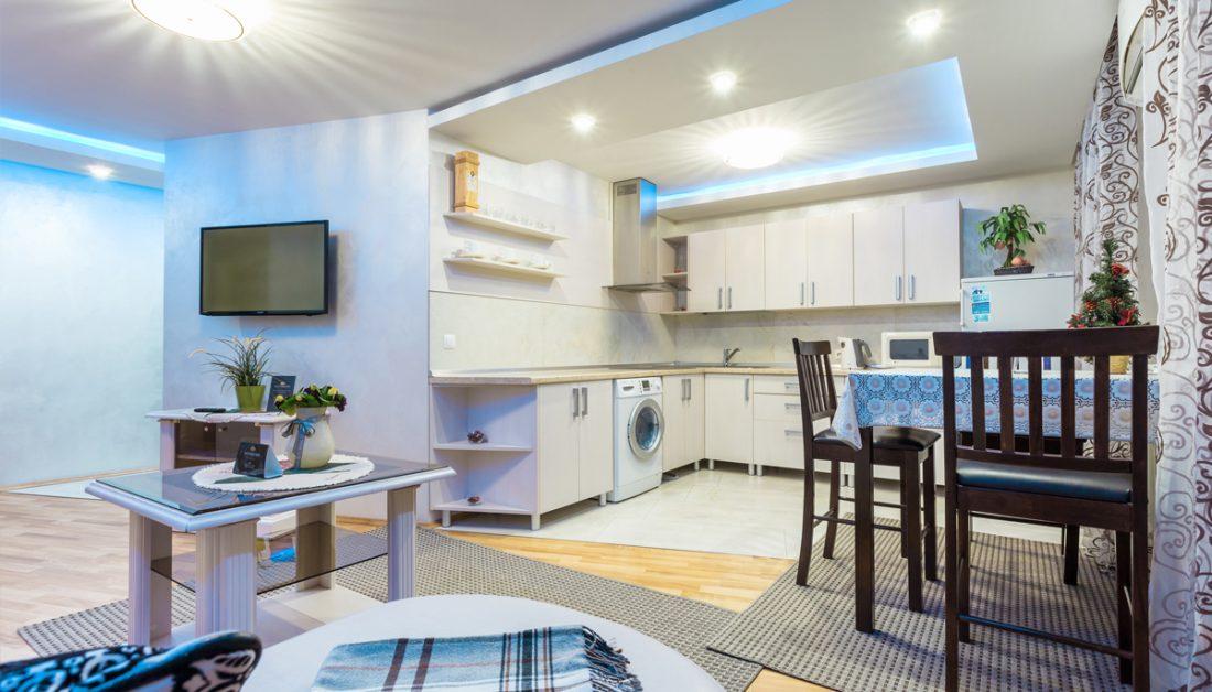 Idee für ein kleines Appartement im Dach - Große Küchenische mit Esstisch & Stühlen aus Holz - Beistelltisch & Beistellschrank im Wohnbereich - Teppiche